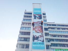 Advertising banner on a building install