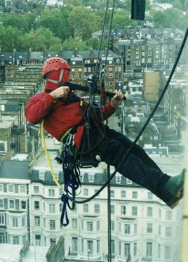 Abseiler jet-washing a commercial building